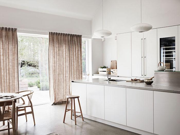 exemple d amenagement cuisine blanche avec ilot central doté de plan de travail gris, sol gris, rideaux couleur grege