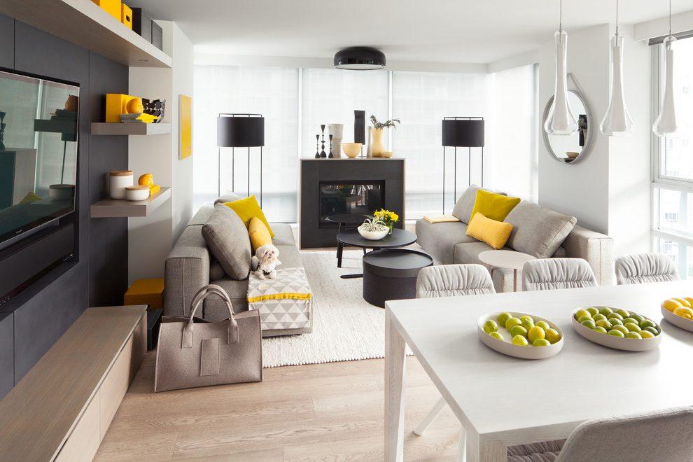 salon gris et blanc avec accents jaunes, canapés gris taupe, cheminée et tables basses noires, parquet clair, miroir rond, table salle à manger blanche, mur d accent noir