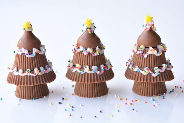 arbre de noel de bonbons au chocolat avec decoration glaçage blanc, petites billes colorées et étoiles jaunes de sucre