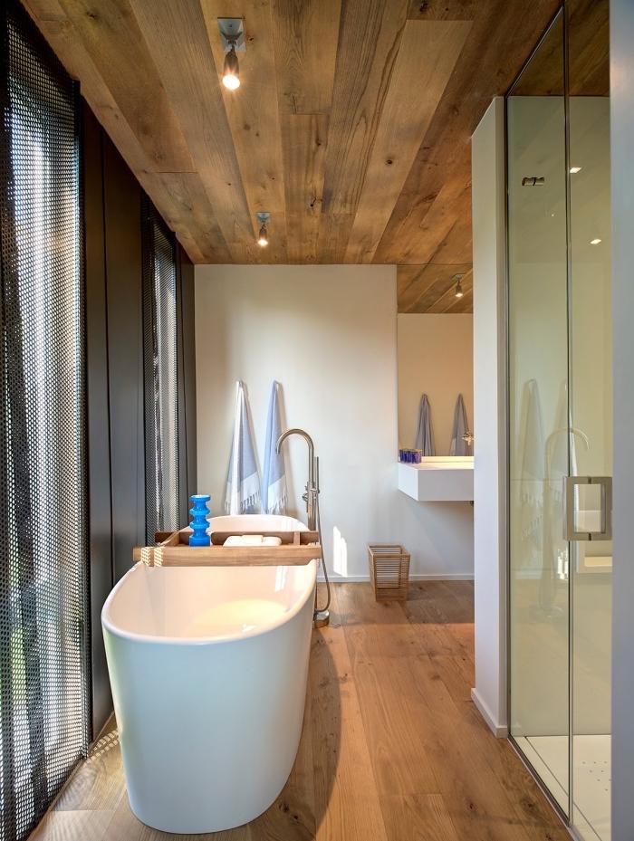 plancher salle de bain, aménagement pièce aux murs blancs et plafond en bois massif avec portes coulissantes noires