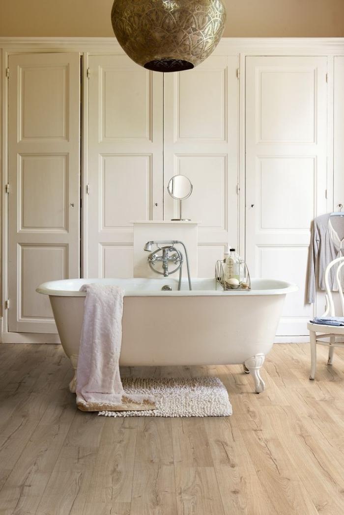 revetement salle de bain, modèle de baignoire blanche sur plancher en bois et tapis moelleux en blanc