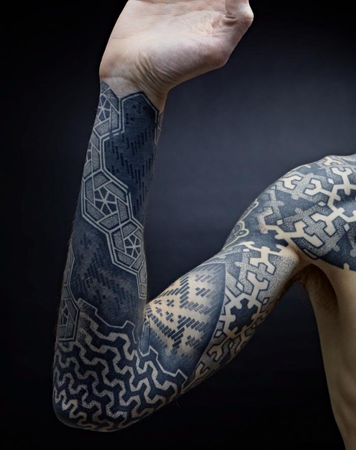 tatouage tribal homme, dessin en encre sur le bras masculin aux motifs triangulaires et puzzle