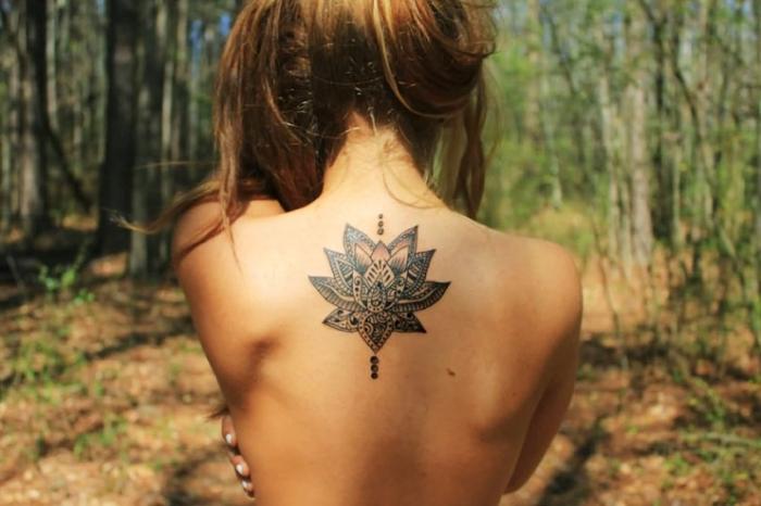 tatouage feminin, dessin sur le dos à design lotus en motifs mandala, art corporel aux motifs floraux