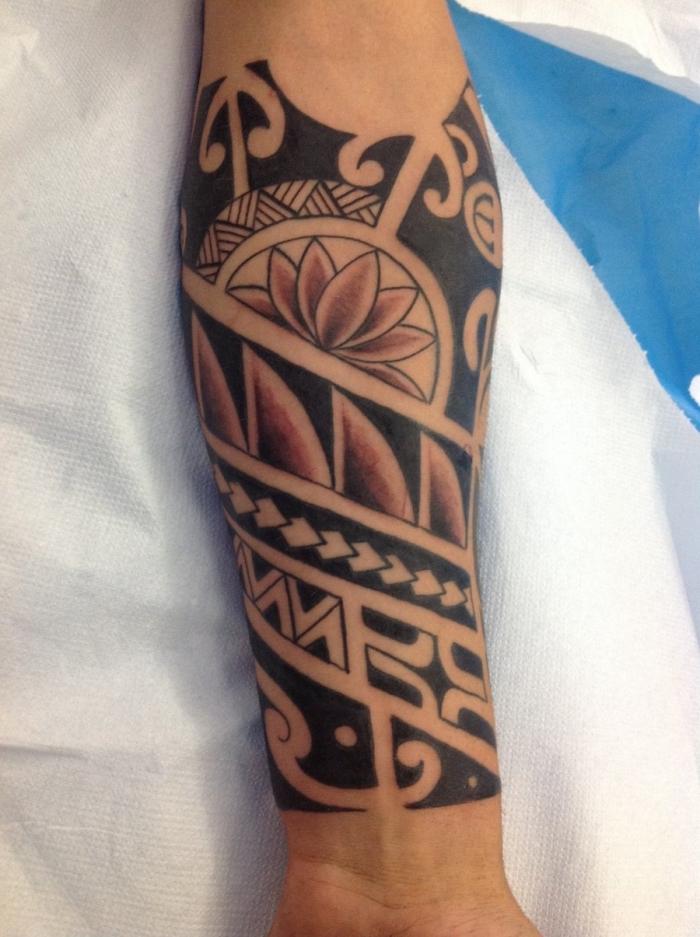 modele tatouage, dessin rouge et noir sur le bras à design lotus et motifs géométriques et tribal
