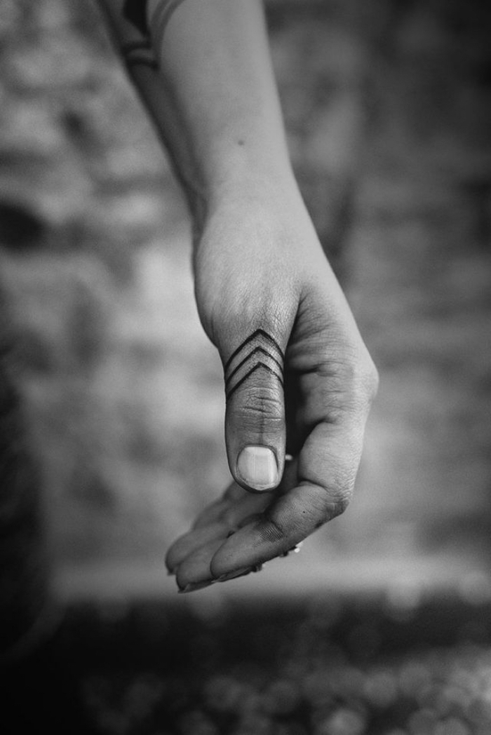 modele tatouage, dessin en encre sur les doigts et les bras à design tribal et motifs triangulaires
