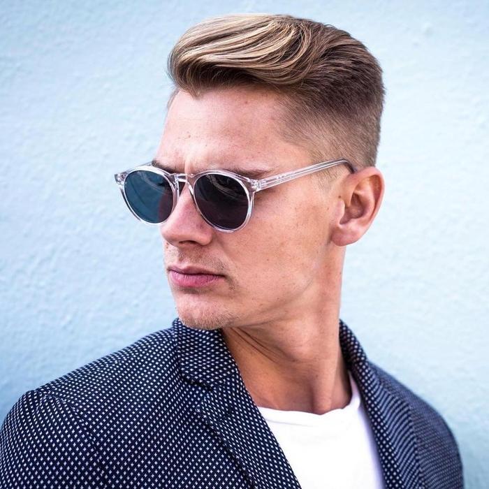 une coupe dégradé homme élégante et chic avec des cheveux tondus sur les côtés et une mèche longue peignée en arrière