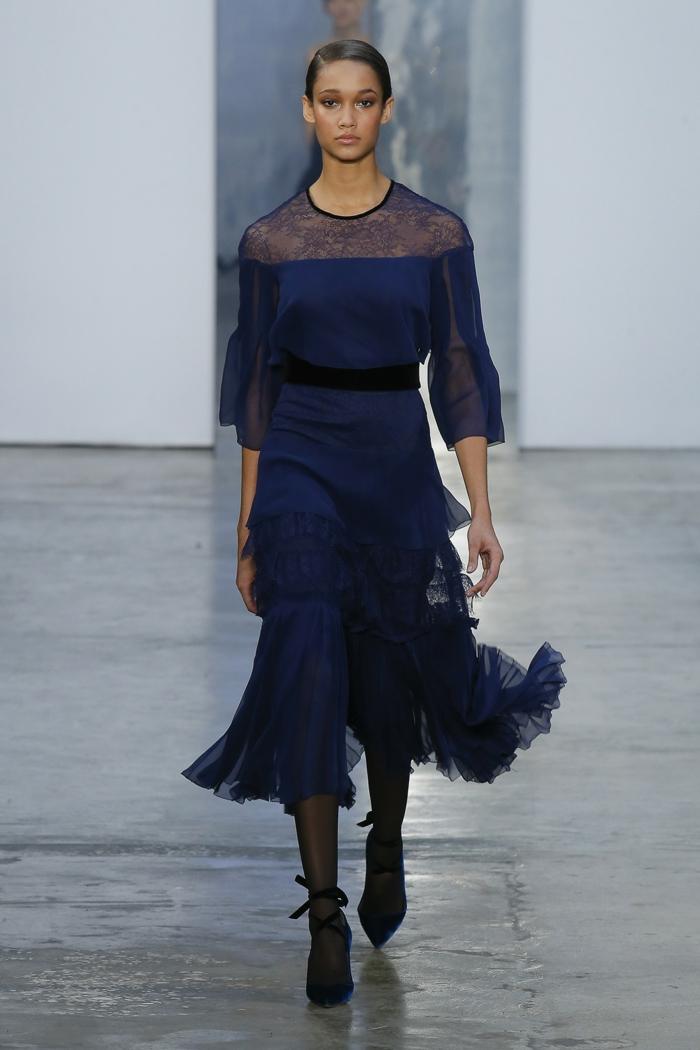 robe de cocktail pour mariage en bleu royal avec des manches 3/4, plissés dans la partie basse, dentelle autour du cou et sur les manches, ceinture noire, chaussures noires pointues avec des nœuds papillons sur les chevilles
