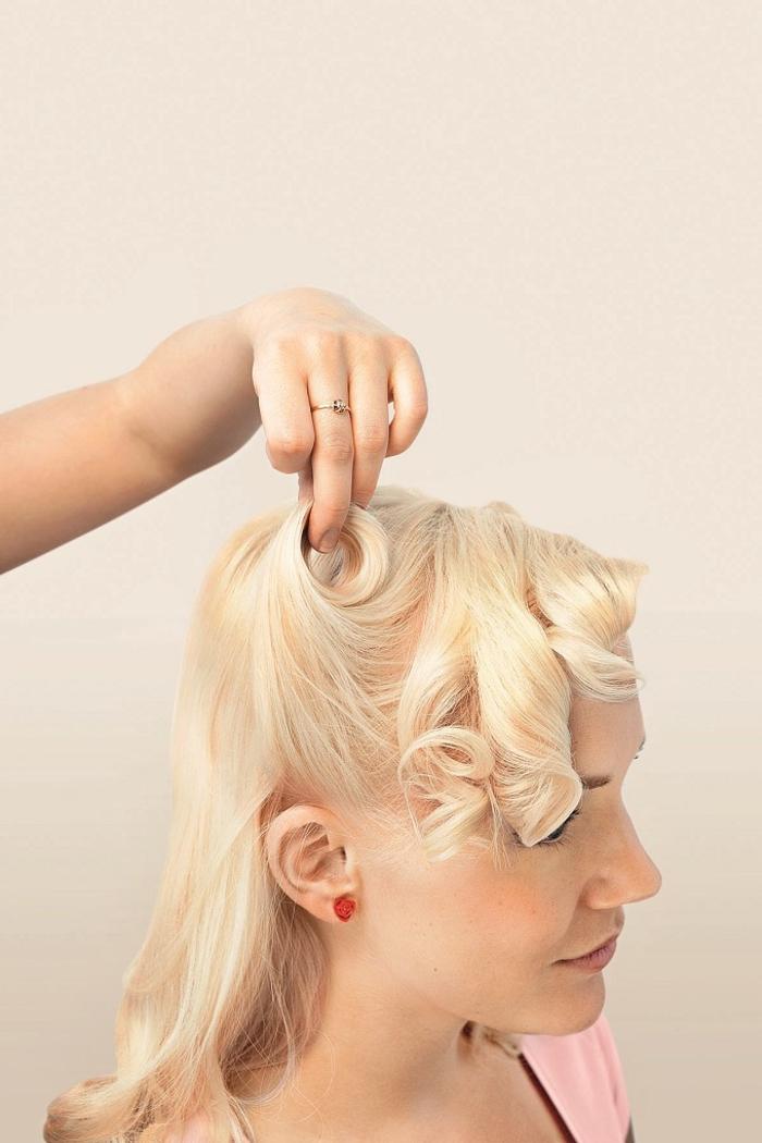 tuto pour réaliser une coiffure pin up facile avec des mèches torsadées relevées des deux côtés de la tête