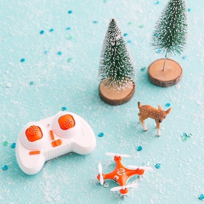 un drone miniature en orange et blanc, petits figurines de sapin de noel et biche, cadeau de noel ado garcon