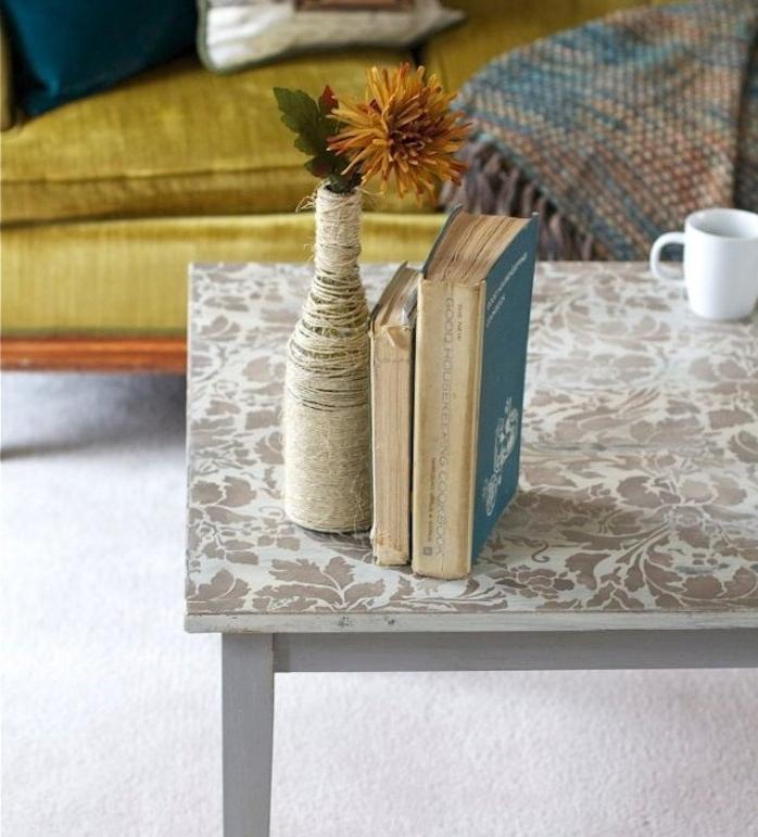 relooker une meuble, table décorée à motifs floraux créés au pochoir, livres, bouteille décorée de ficelle, canapé style oriental