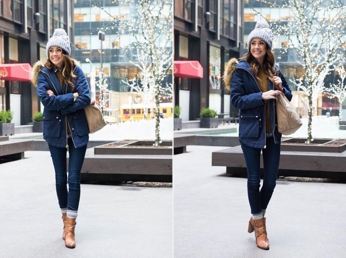 manteau capuche fourrure, femme habillée en jeans et manteau bleu foncé avec bottines marron et bonnet gris