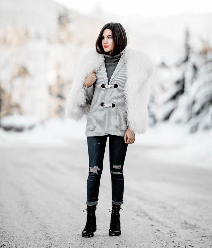 tenue hiver, modèle de jeans foncés déchirés portés avec gilet et pull gris, bottines avec lacets et manteau faux fur blanc