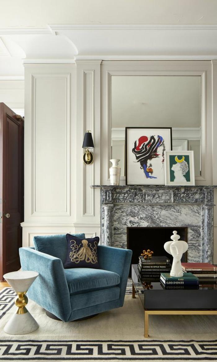 salon moderne de luxe, cheminée en marbre noir et blanc, fauteuil en velours bleu pastel, miroir avec deux appliques latérales de côté aux abat-jours noirs, tapis en beige et noir