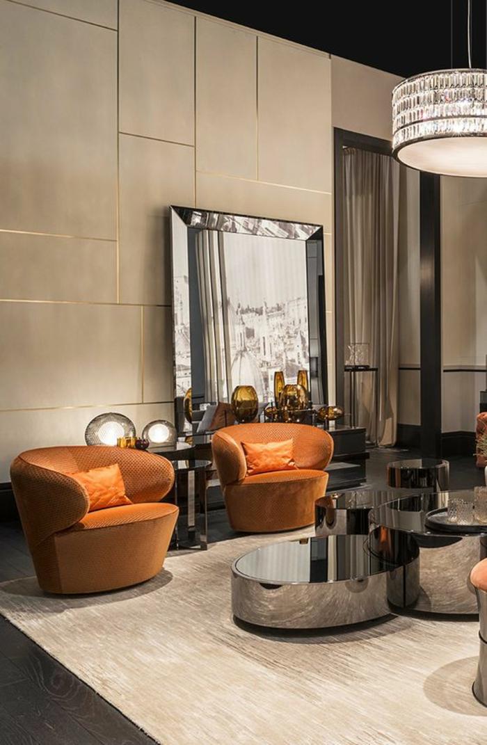 salon moderne de luxe avec des surfaces brillantes en nuances argent, grand luminaire au plafond en forme de tambour avec des cristaux Swarovski brillants, grand miroir appuyée contre le mur en forme rectangulaire, table avec plusieurs niveaux aux surfaces miroitantes