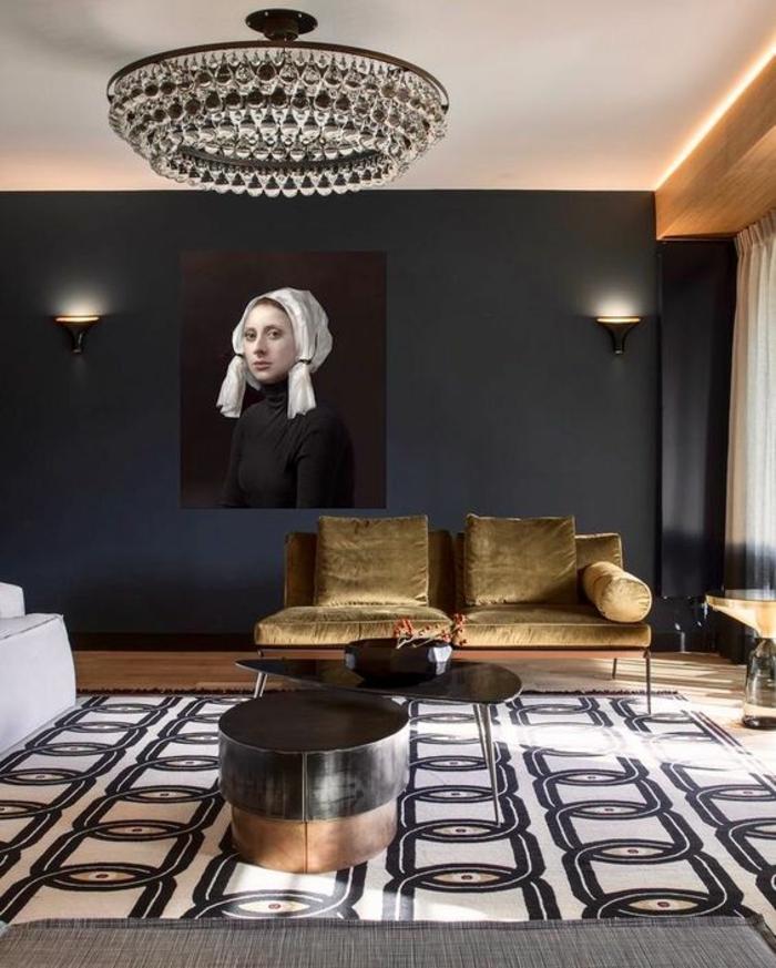 deco salon design avec des meubles en couleur tabac, tableau style XV-ème siècle, grand luminaire rond en forme de tambour avec des grandes pampilles en cristal, tapis avec des motifs chaines en noir et blanc