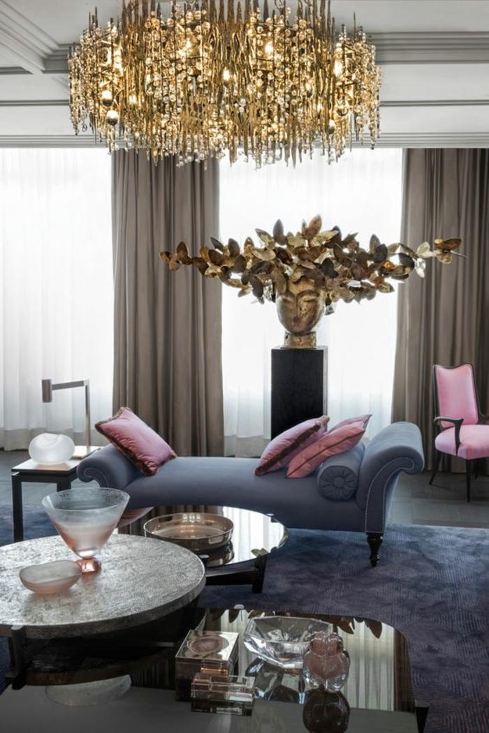 maison moderne de luxe avec un grand luminaire massif doré très brillant, statuette avec visage de femme aux cheveux qui représentent une multitude de papillons, canapé en gris pastel, coussins roses et fauteuil en rose et gris, rideaux en taupe