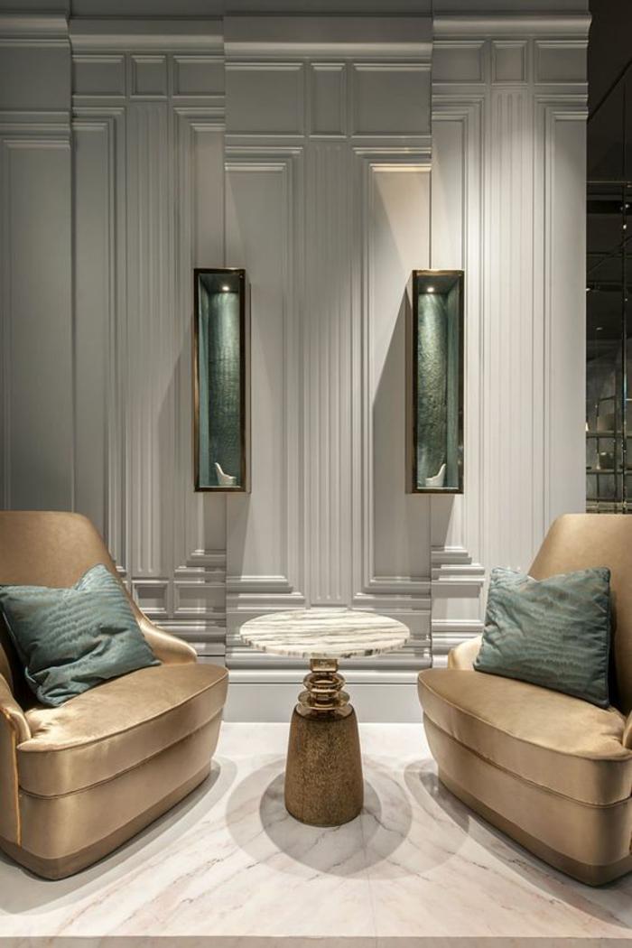 salon de luxe, deco sejour, ambiance classe, style des murs néo classique, fauteuils massifs en couleur bronze avec des coussins en vert pétrole, table ronde en blanc et bronze