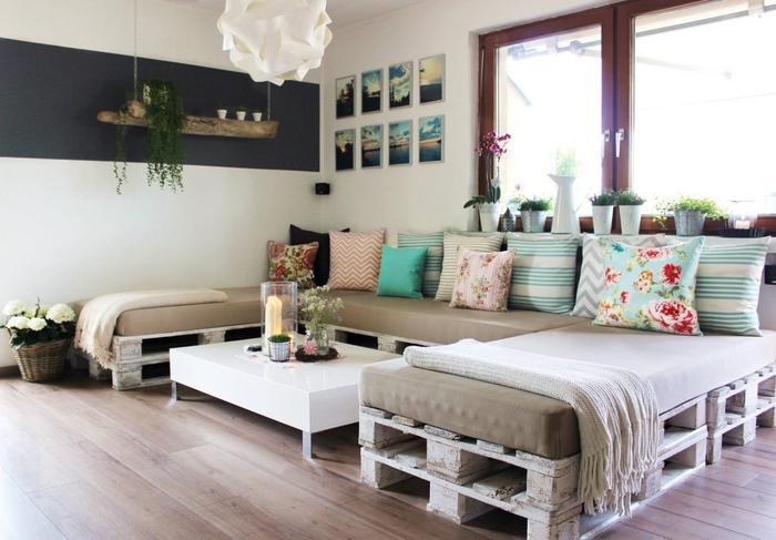 canapé d'angle en palette avec des coussins dépareillés en nuances pastel et motifs différents, meuble palette confortable et fonctionnel