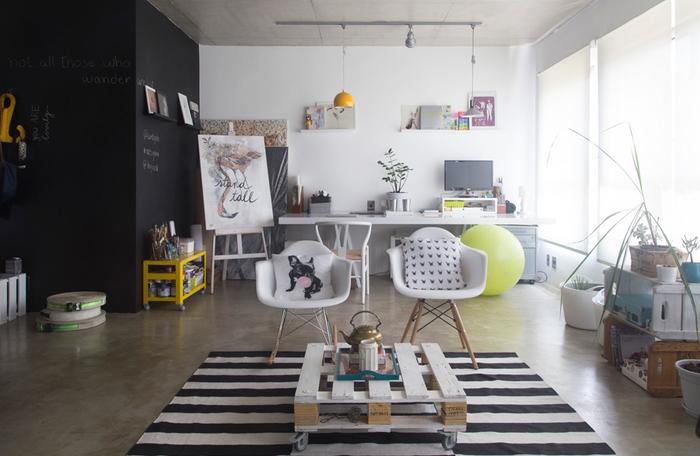 un salon de style loft industriel en noir et blanc avec une table basse en palette assortie avec des chaises scandinaves et un tapis à rayurers