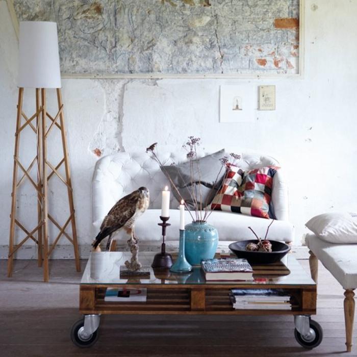 une table basse palette avec roulettes et plateau en verre d'aspect vintage qui s'accorde avec la déco blanche