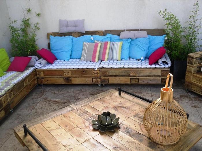 un salon de jardin fabriqués entièrement en palettes acec des coussins et , des meubles palettes de jardin fonctionnels et confortables