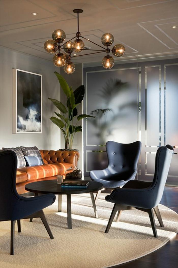 idée deco salon avec des fauteuils en gris anthracite et table ronde en noir, luminaire en métal avec une dizaine de boules en verre effet fumé, tableau en nuances blanches et grises avec cadre blanc, tapis rond en beige effet de moquette, parquet noir