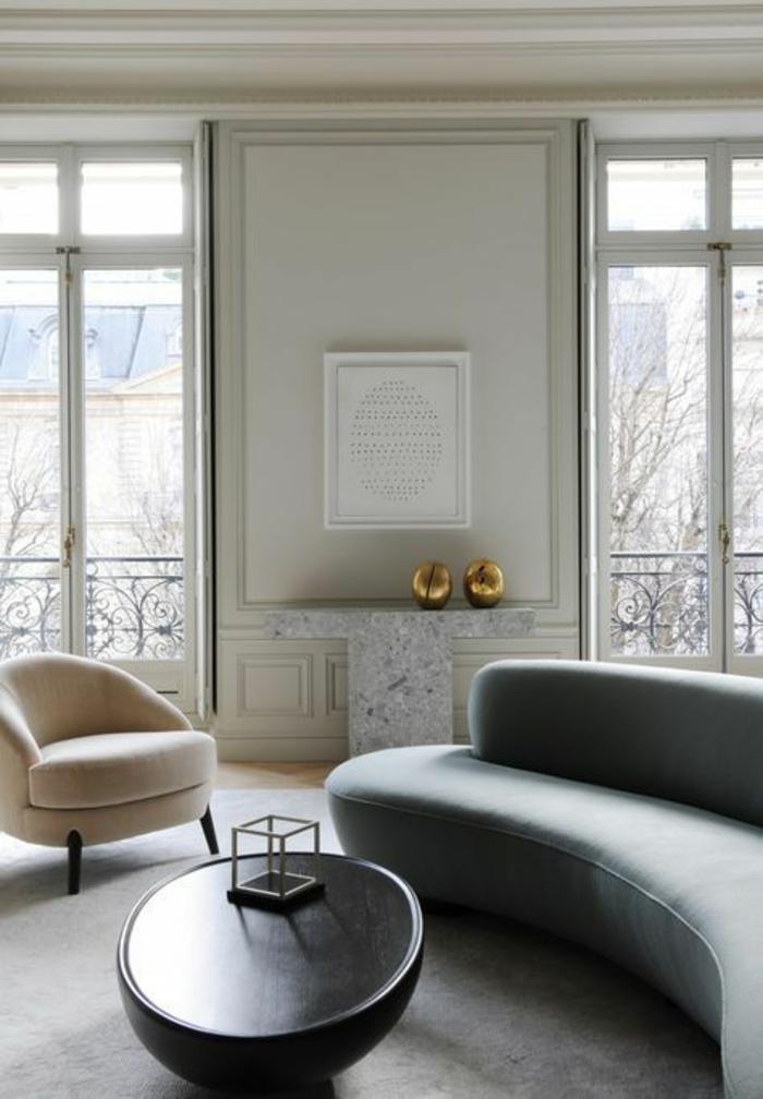 deco salon design avec un canapé en gris et en couleur crème, table ronde en noir avec objet déco en forme carrée, mur en vert pistache, deux objets déco dorés ronds