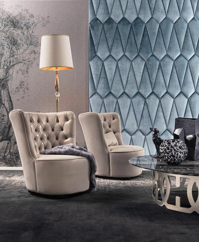 deco sejour avec un mur revêtu de tissu velouté en bleu pétrole, luminaire sur pied avec abat-jour blanc crème, deux fauteuils en style art déco blanc crème en cuir, table ronde avec base ronde argentée et plan en verre trempé noir