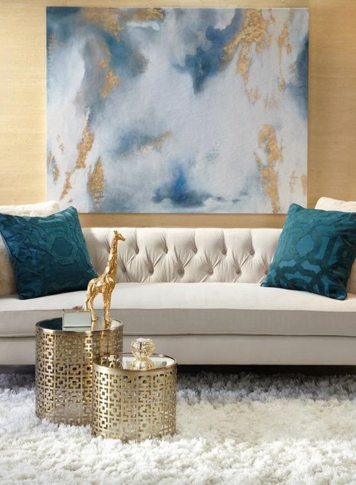 deco salon, amenagement salon, maison moderne de luxe, grand panneau au mur en nuances blues, blanches et dorées, deux petites tables rondes en métal ajouré doré, canapé blanc avec deux coussins en bleu pétrole, tapis blanc moelleux douceur, murs en beige doré