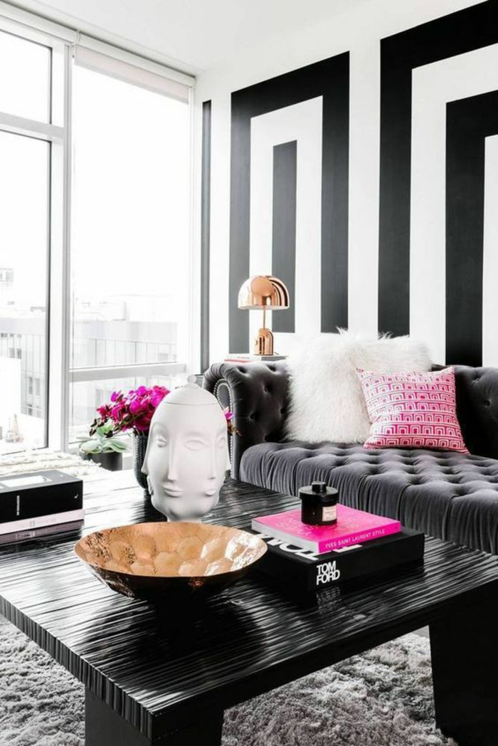 salon moderne de luxe avec canapé en gris anthracite, murs aux motifs graphiques en noir et blanc, table carrée en matière PVC noire, tapis en gris pastel, objet déco visage aux multiples faces