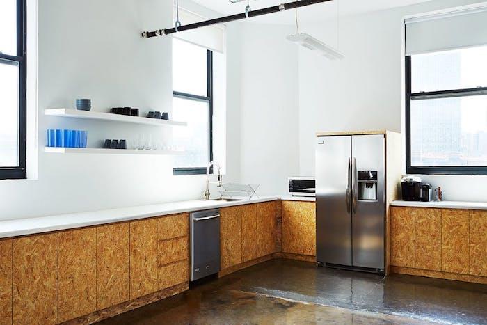 cuisine amenagee avec meubles bas en bois et plan de travail blanc, etageres blanches, electromenager inox, sol en zinc