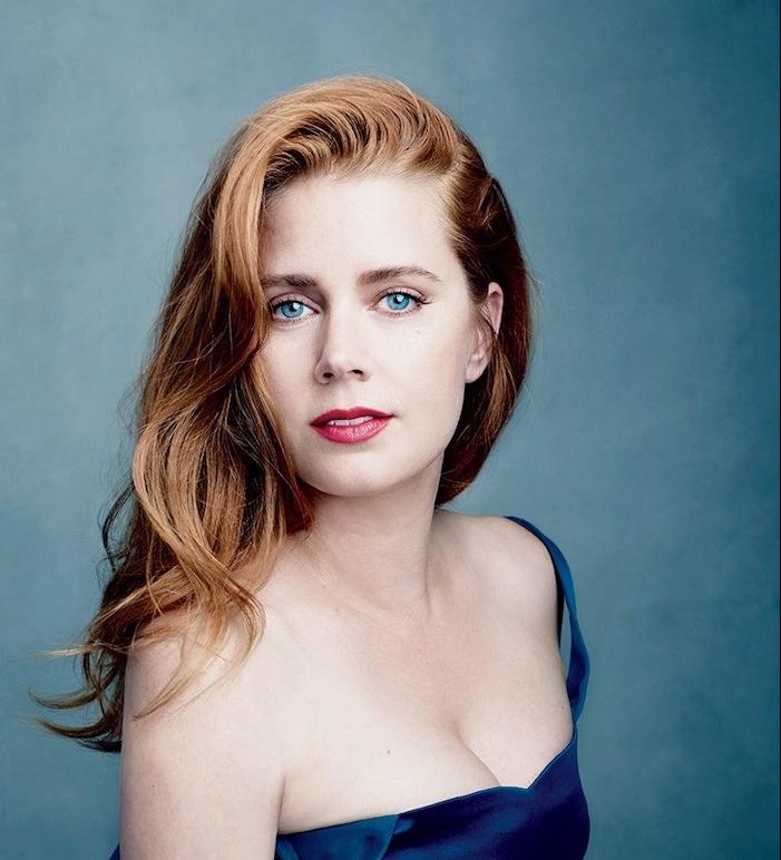 amy adams avec coloration rousse, cheveux cuivrés sur le côté avec de légères ondulations, robe bleu marine