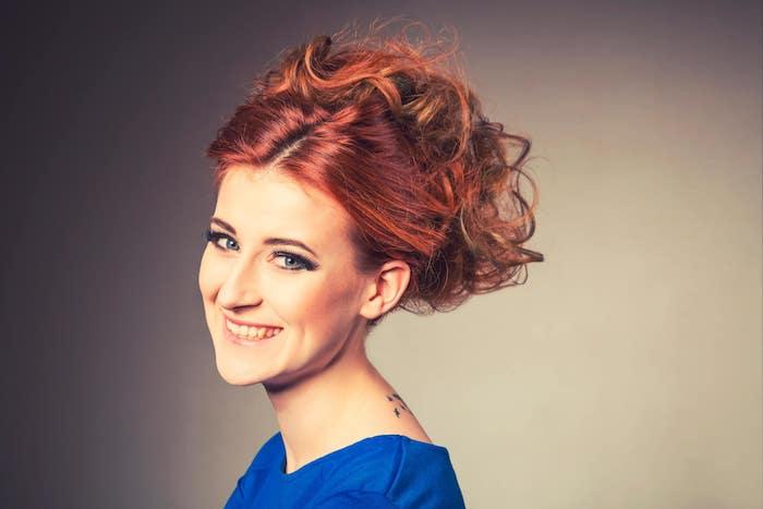 exemple de coloration rouge aux éclats roux, balayage cuivré intéressant, cheveux attachés en arrière avec volume et robe bleue