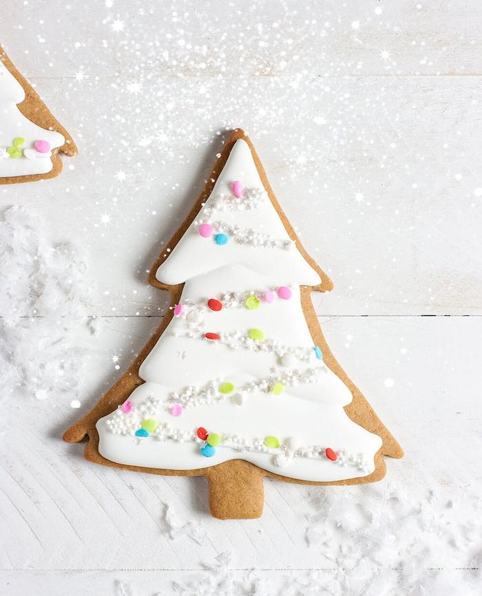 idée de biscuit en pain d épices en forme de sapin décoré de glacage sucre glace blanc décoré de guirlande coloré de billes sucrées
