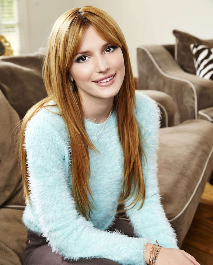 exemple de couleur cheveux blond cuivré, coupe dégradé femme avec frange et pull bleu, canapé gris marron