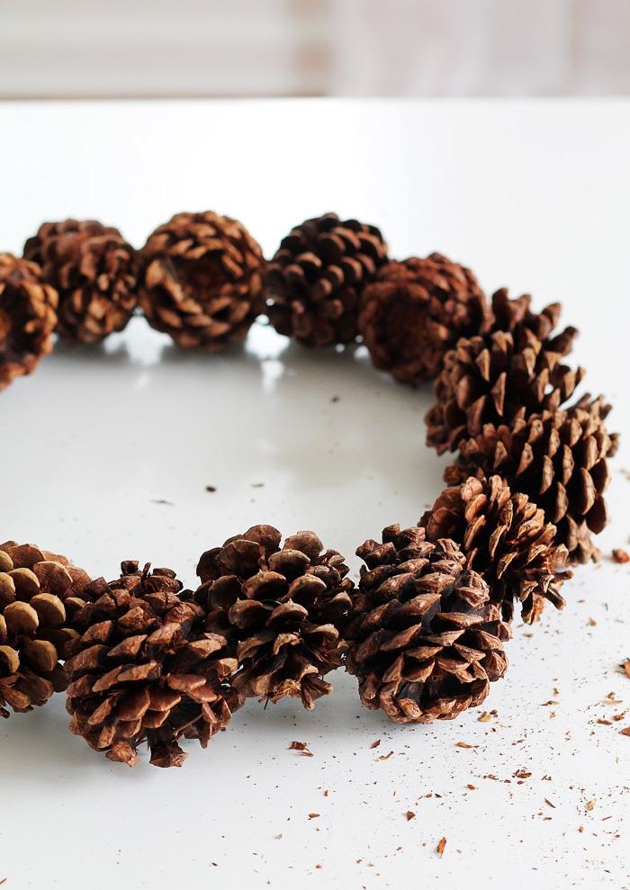 couronne de noël toute naturelle réalisée avec des pommes de pin fixées à un fil de fer, idée deco noel faire soi meme