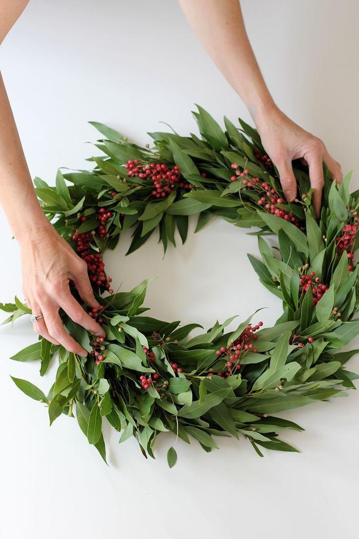 retour à la simplicité avec une couronne de l'avent toute végétale en feuilles de laurier et fruits rouges, un diy noel pour réaliser une déco naturelle