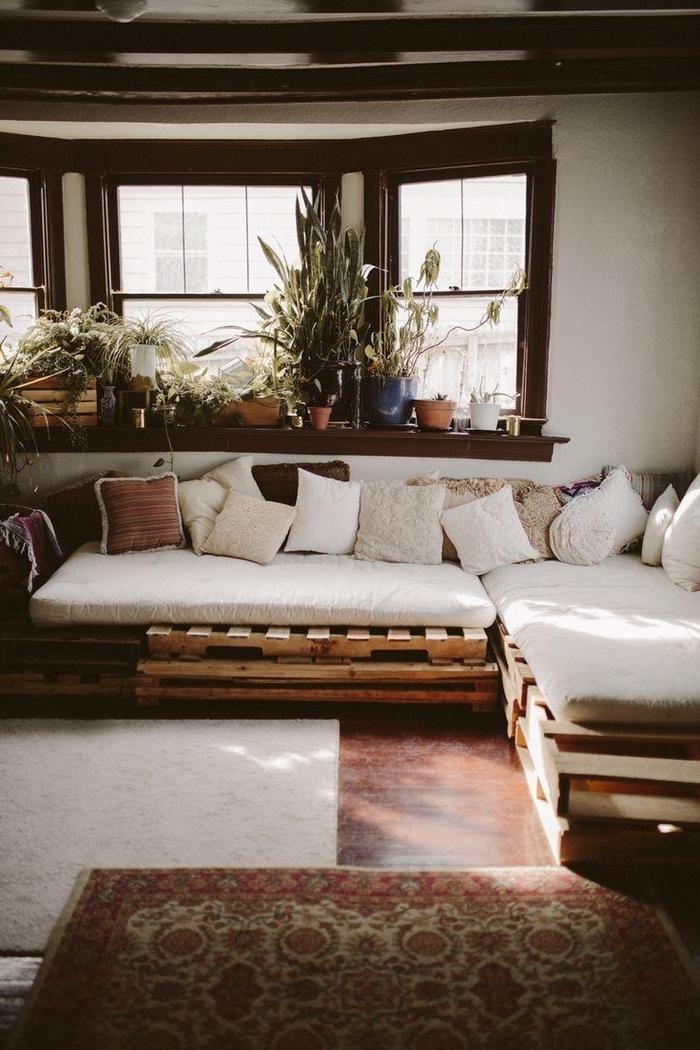 grand canapé d'angle fabriqué avec des palettes transformé en coin de repos bohème chic grâce aux nombreux coussins