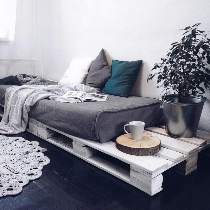 un canapé-lit en palette avec de la place de côté pour ranger des affaires