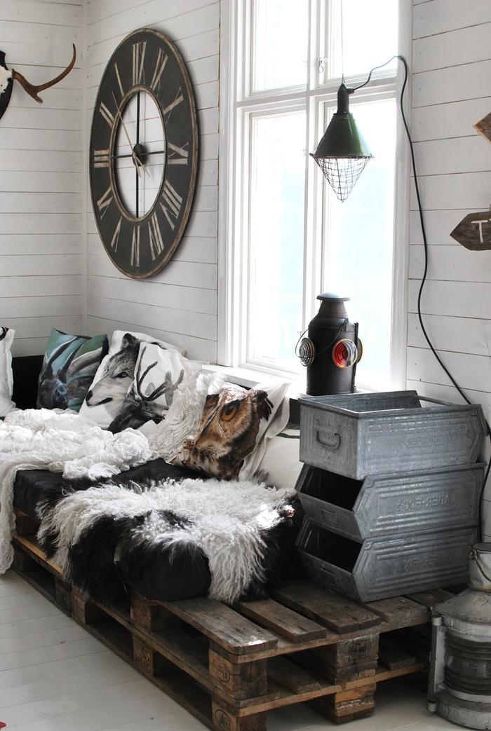une chambre aménagée dans un mélange de styles industriel et bohème chic avec un canapé en palette cosy