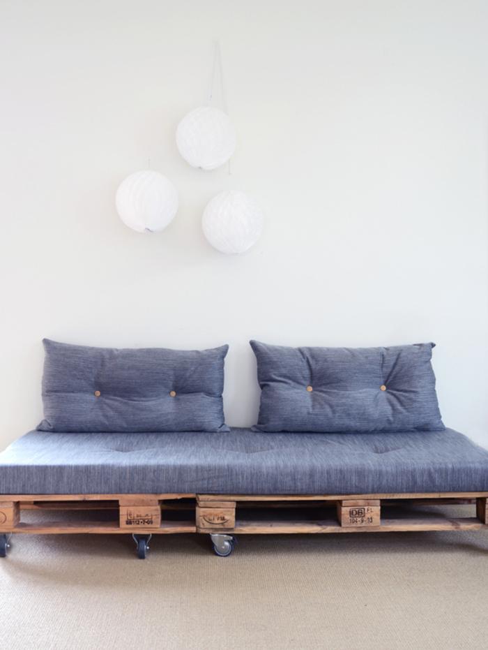 un petit canapé en palette avec roulettes, matelas et coussins matelassés idéal pour l aménagement d un salon moderne de style scandinave