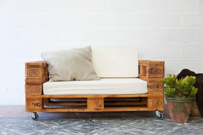 un canapé en palette deux places avec roulettes aux lignes simples avec coussins et matelas pour un maximum de confort