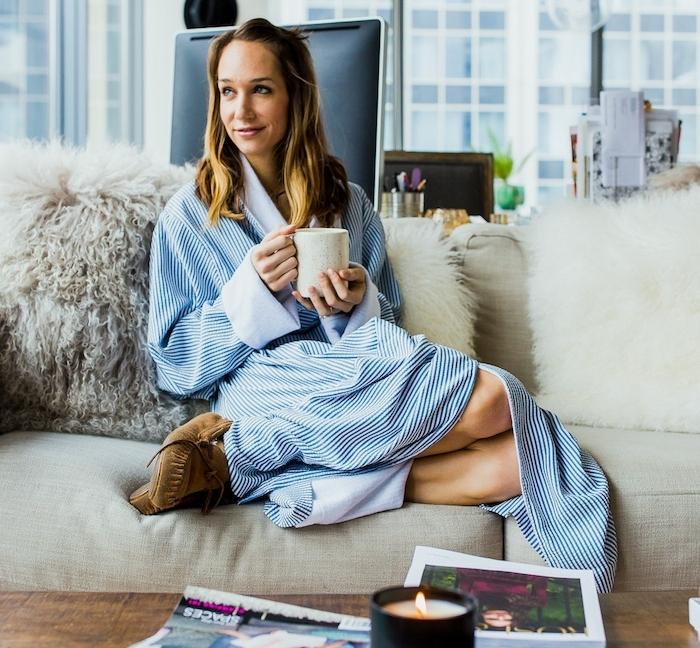 modele de canapé pas cher en gris avec des jetés de peau animale, femme en peignoir qui boit son café, deco cocooning