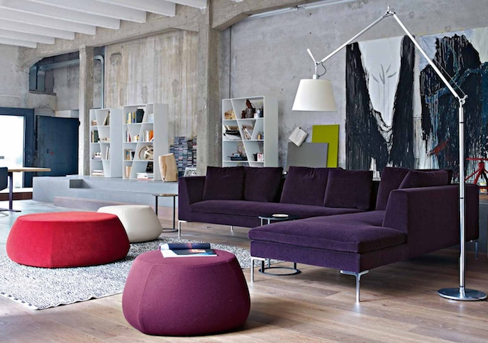 déco loft industriel dans un salon contemporain avec canapé violet, tables basses en mauve, blanc et rouge, tapis rouge, parquet clair, etagere livres, mur usé