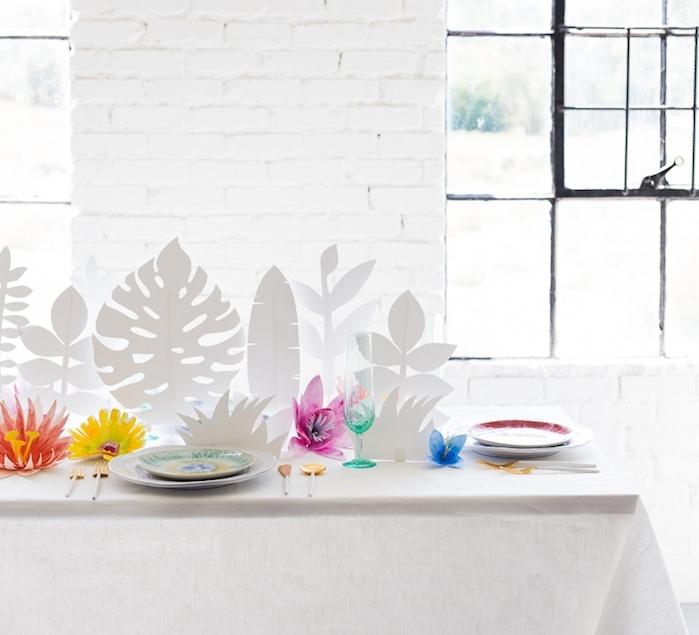 centre de table de feuilles tropicales blanches et diy fleur en papier coloré dans une salle blanche avec mur en briques et table recouverte de nappe blanche