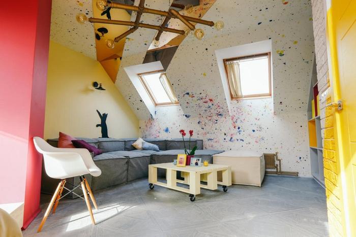 aménagement d'une chambre sous combles moderne et artistiques aux accents de couleurs vives sur les murs et un mobilier de style scandinave avec une table basse palette