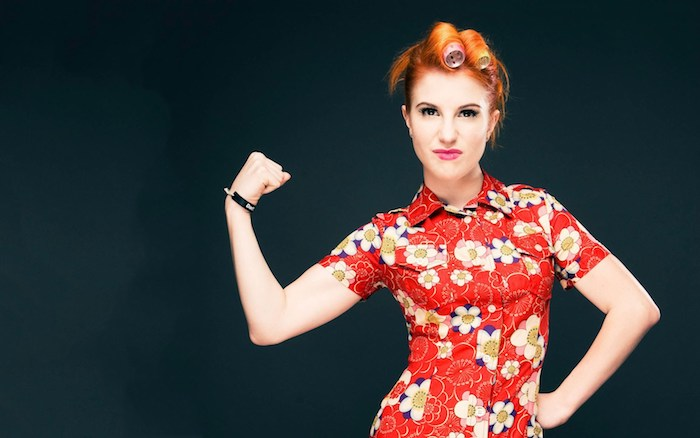 hayley williames et sa coloration rousse, cheveux mi long roux avec des bigoudies et robe rouge à fleurs colorées