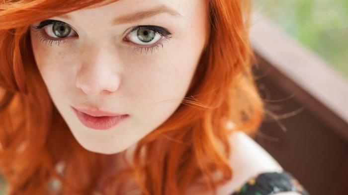 couleur cuivrée, jeune femme aux yeux verts et cheveux de coloration orange, maquillage pour yeux verts aux lèvres nude