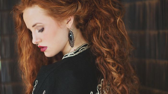 roux cuivré, couleur de cheveux flamboyant pour chevelure longue ondulée, veste noire à motifs blancs