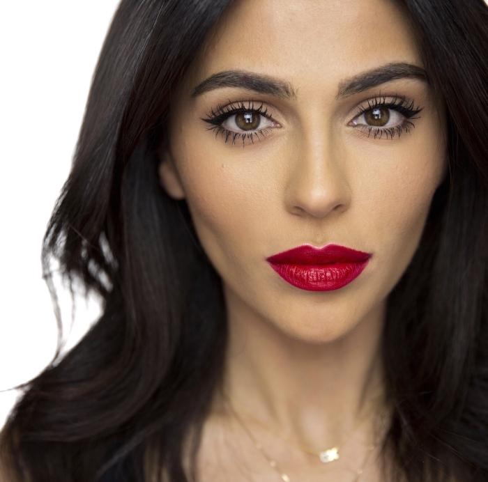 brunette aux cheveux longs légèrement bouclés avec maquillage à lèvres rouge et eye-liner noir